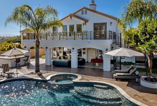 Mediterranean Exterior of Home with French doors, Pool with hot tub, Outdoor kitchen, Gate, Raised beds, Pathway, Fence