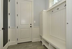 Country Mud Room with Standard height, stone tile floors, Chair rail, Built-in bookshelf, soapstone tile floors, Wainscotting