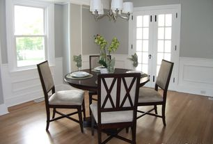 Traditional Dining Room with Chandelier, Crown molding, Wainscotting, Laminate floors, Chair rail, French doors