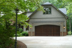 Traditional Garage with Garage door with recessed panels, Wall sconce, Large wooden garage door with arched top