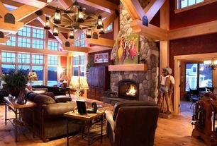 Country Living Room with picture window, Large wagon wheel chandelier with rustic lanterns, Exposed beam, stone fireplace