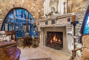 Traditional Living Room with High ceiling, limestone floors, stone fireplace, Arched window, Built-in bookshelf, Fireplace