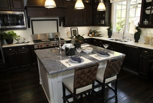 Traditional Kitchen with Laminate wood floor, Wolfe - 6 burner + griddle, double oven, Glass panel, electric cooktop, Flush