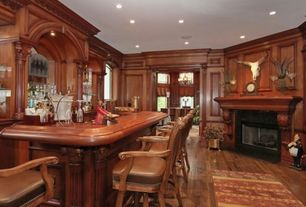 Traditional Home Office with stone fireplace, Crown molding, Hardwood floors, Arched window, Chair rail, can lights