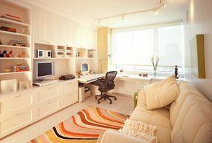 Modern Home Office with Laminate floors, Standard height, specialty window, Pendant light, Built-in bookshelf