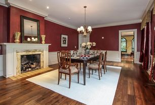 Traditional Dining Room with Wainscotting, Hardwood floors, Chandelier, Crown molding, stone fireplace