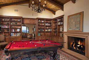 Mediterranean Game Room with Cement fireplace, Hardwood floors, Built-in bookshelf, Exposed beam, High ceiling, Chandelier