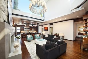 Contemporary Great Room with stone fireplace, Armstrong oak sunset west, Lazar swivel chair, Chandelier, Skylight