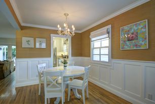 Traditional Dining Room with Crown molding, Chandelier, Laminate floors, Wainscotting