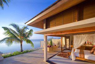 Tropical Master Bedroom with specialty door, Built-in bookshelf, Florida tile berkshire wood look tile, Hardwood floors