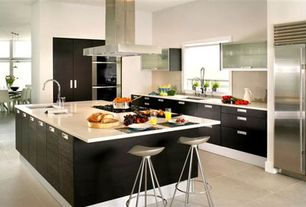Contemporary Kitchen with limestone tile floors, Flush, Corian counters, Island Hood, Kitchen island, High ceiling, L-shaped