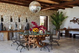Eclectic Dining Room with Pendant light, Exposed beam, Built-in bookshelf, limestone floors, Standard height