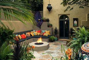 Eclectic Patio with Fire pit, Multicolored outdoor accent pillows, Stone tile and gravel floors, Arched window, Fence