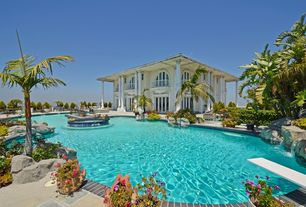 Tropical Swimming Pool with Raised beds, exterior stone floors, Fence, Pool with hot tub, Arched window, French doors