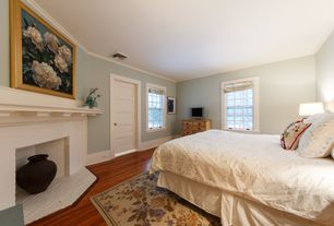 Cottage Guest Bedroom with Crown molding, specialty door, Laminate floors, Cement fireplace