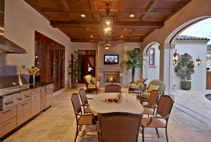 Mediterranean Patio with exterior stone floors, picture window, French doors, Outdoor kitchen, Fence, Transom window