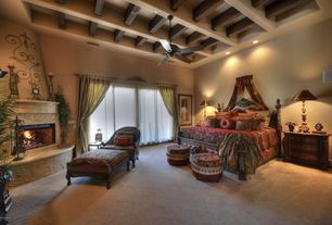 Mediterranean Master Bedroom with metal fireplace, Ceiling fan, Carpet, Cement fireplace, Exposed beam ceiling, Exposed beam