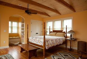 Country Guest Bedroom with Hardwood flooring, Ceiling fan, Exposed wood ceiling, Exposed beam, Hardwood floors, Window seat