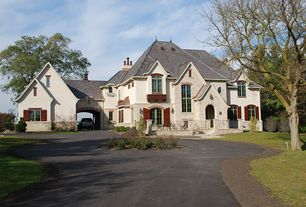 Traditional Exterior of Home with Arch door, Shingle roof, Roundabout driveway, Gable roof, Wood shutters, Arch window