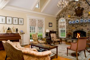 Traditional Living Room with Crown molding, Wainscotting, Exposed beam, Arched window, stone fireplace, French doors