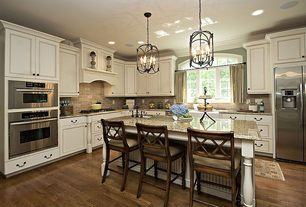 Traditional Kitchen with Custom hood, Stone Tile, double wall oven, Built In Refrigerator, Inset cabinets, Kitchen island