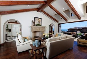 Mediterranean Living Room with Exposed beam, stone fireplace, Skylight, Hardwood floors, High ceiling
