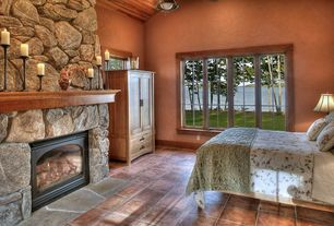 Rustic Guest Bedroom with Cathedral ceiling, Pendant light, metal fireplace, terracotta tile floors, stone fireplace