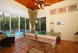 Tropical Game Room with Ceiling fan, sliding glass door, picture window, terracotta tile floors, can lights, Standard height