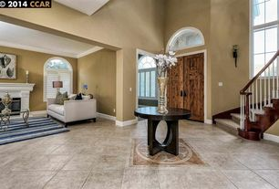Traditional Entryway with Arched window, High ceiling, travertine tile floors, Transom window, stone fireplace