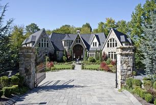 Traditional Exterior of Home with slate floors, Stone gate posts, Wrought iron gate