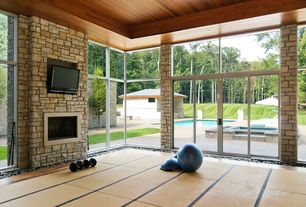 Contemporary Home Gym with Transom window, tv wall mount, Pure Fitness Exercise Ball with Pump, stone fireplace