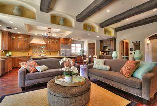 Mediterranean Great Room with Hardwood floors, Chandelier, Leopard Ottoman / Coffee Table, Wall sconce, specialty door