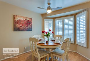 Traditional Dining Room with Crown molding, Upholstered dining chair, Bay window, Painted wood blinds, Ceiling fan
