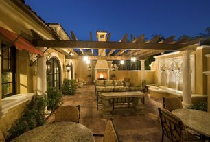 Mediterranean Patio with exterior awning, double-hung window, Exterior fireplace, Trellis, Doric column, Fence, Casement