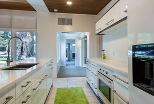 Contemporary Kitchen with wall oven, large ceramic tile floors, 2 in. Solid Surface Countertop in Arctic White, Galley, Flush
