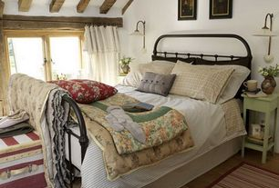 Country Master Bedroom with Hardwood floors, Exposed beam, Casement, bedroom reading light, Standard height