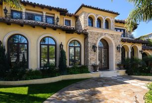 Mediterranean Exterior of Home with Fence, Paint, Deck Railing, Arched window, French doors, Raised beds, Transom window