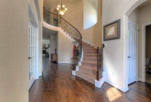 Traditional Staircase with curved staircase, High ceiling, Hardwood floors