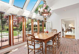Country Dining Room with Chandelier, Standard height, picture window, Skylight, can lights, French doors, Brick floors