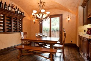 Mediterranean Dining Room with Chandelier, Built-in bookshelf, Wall sconce, Hardwood floors, French doors