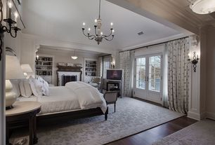 Traditional Master Bedroom with Chandelier, Cement fireplace, flush light, Area rug, French doors, Wall sconce, Crown molding