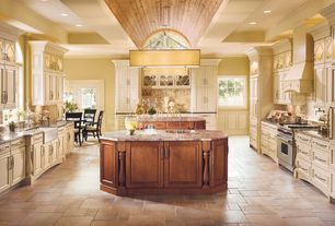 Traditional Kitchen with Kitchen island, stone tile floors, Arched window, Simple granite counters, Limestone Tile, gas range