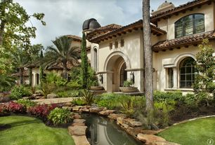 Mediterranean Exterior of Home with exterior stone floors, Raised beds, Pond, French doors, Arched window, Pathway