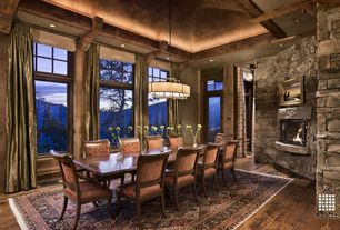 Rustic Dining Room with Fireplace, Hardwood floors, Exposed beam, Glass panel door, High ceiling, stone fireplace, can lights