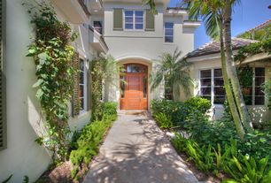 Tropical Front of Home with six panel door, exterior stone floors, Pathway, Transom window, cement siding, Casement