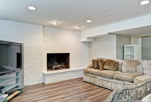 Rustic Living Room with Standard height, Fireplace, Hardwood floors, Exposed brick, can lights, Painted brick