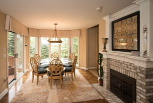 Traditional Dining Room with Hardwood floors, metal fireplace, Pendant light