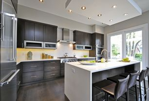 Contemporary Kitchen with Breakfast bar, Kitchen island, Corian counters, electric cooktop, Wall Hood, double wall oven