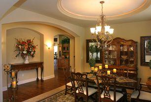 Mediterranean Dining Room with Chandelier, Hardwood floors, Standard height, Wall sconce
