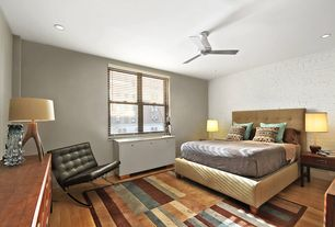 Contemporary Master Bedroom with double-hung window, Built-in bookshelf, can lights, Hardwood floors, interior brick